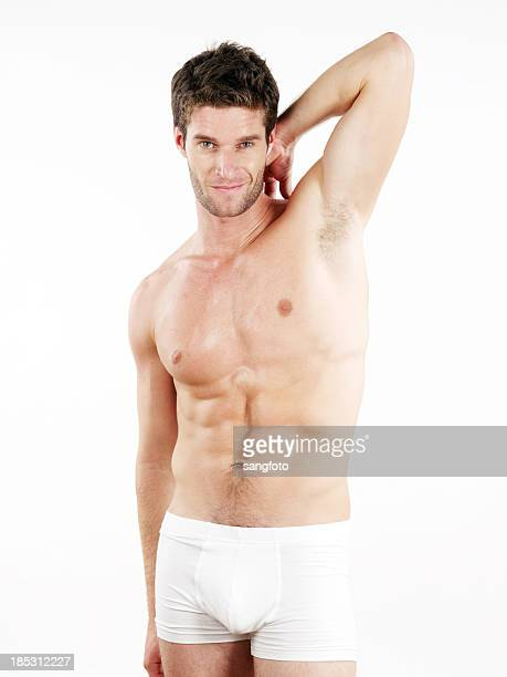 handsome man in boxer shorts hand behind head - boxershort stock pictures, royalty-free photos & images