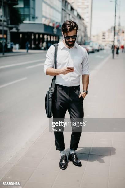 Gut aussehender Mann in Businesswear ist SMS für uber