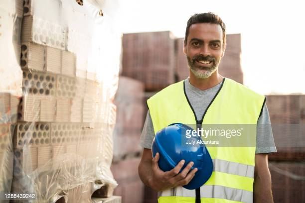 handsome man in construction site portrait with helmet and safety vest. looking at camera near to construction bricks - waistcoat stock pictures, royalty-free photos & images