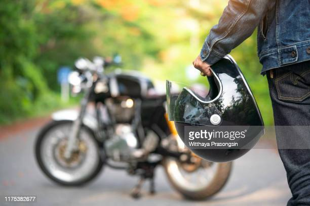 handsome man in jean is holding a helmet and vintage motorcycle blur background - オートバイ競技 ストックフォトと画像