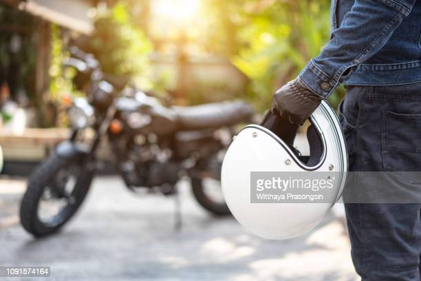 handsome man in jean is holding a helmet - crash helmet stock pictures, royalty-free photos & images