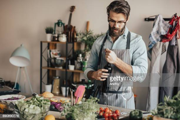 Handsome man in kitchen opening a bottle of red wine