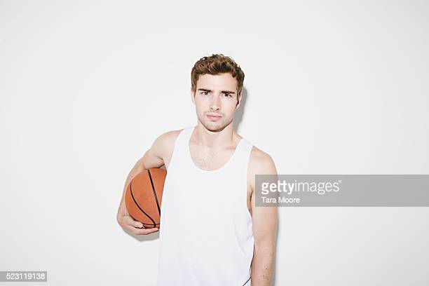 handsome man in studio holding basketball - vest stock pictures, royalty-free photos & images