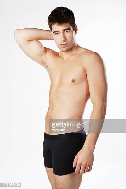 Handsome man in underwear standing hand behind head