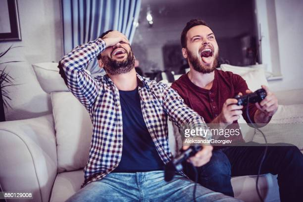 handsome man is defeating his older brother in video games - gamer stock pictures, royalty-free photos & images