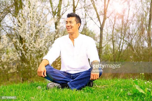 ハンサムな男は屋外での生活を楽しんでいます - 胡坐 ストックフォトと画像