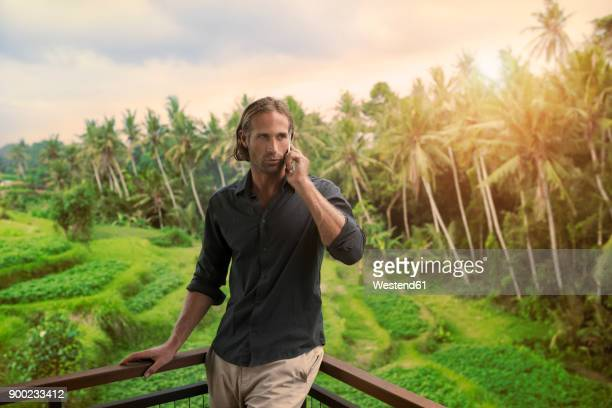 Handsome man leaning on balkony speaking on smartphone with stunning view of tropical landscape