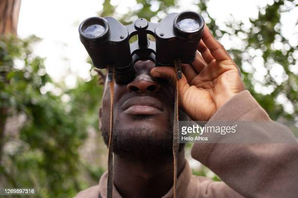 a handsome man looking at something intently through inoculars - searching stock pictures, royalty-free photos & images