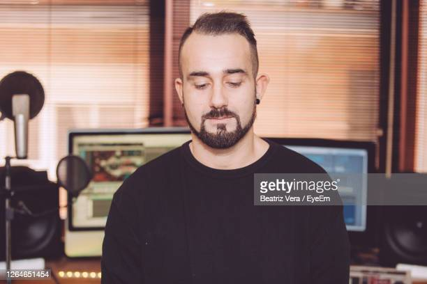 handsome man looking down while standing in recording studio - producer stock pictures, royalty-free photos & images