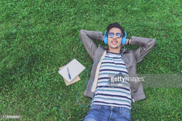 handsome man lying down on the green grass - audio equipment stock pictures, royalty-free photos & images