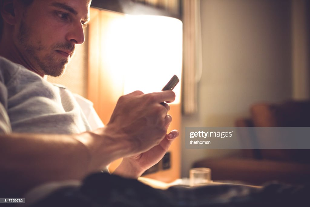 Handsome man lying in bed with mobile phone, Andalusia, Spain : Stock Photo
