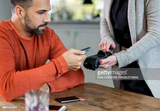 handsome man paying cashless with his credit card