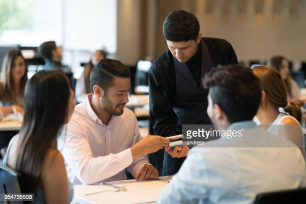 Handsome man paying the waiter with his smartphone at the restaurant looking very happy