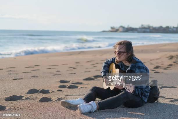 休暇でビーチに座って古典的なギターを演奏ハンサムな男 - ギタリスト ストックフォトと画像