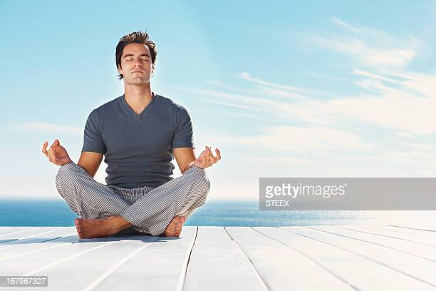 Handsome man practicing yoga outdoors
