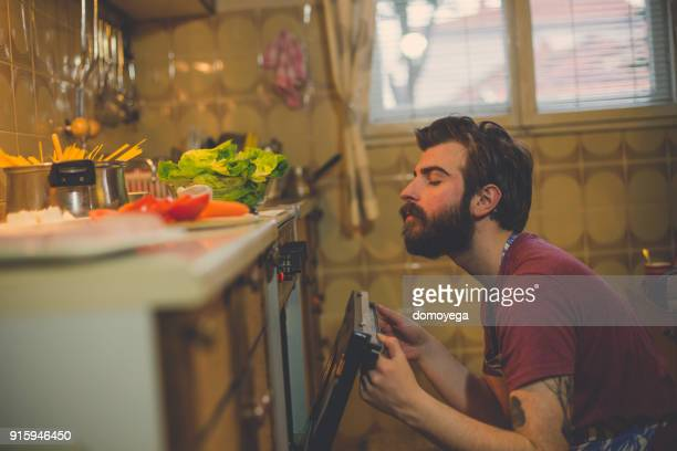Handsome man preparing food in the kitchen at home