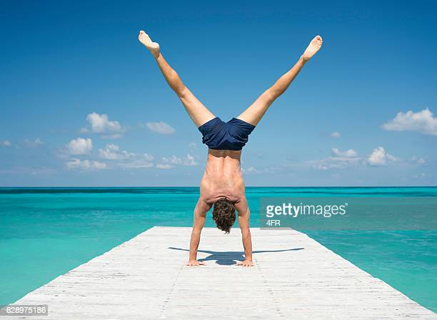 Handsome Man pushing a Handstand on a Pier