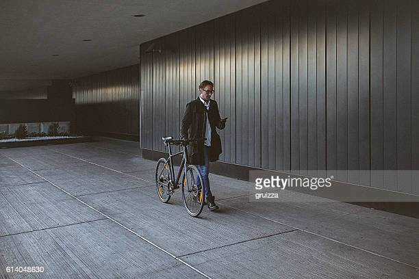Handsome man pushing bicycle beside the grey wall