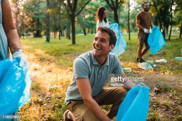 handsome man recycling - selfless stock pictures, royalty-free photos & images