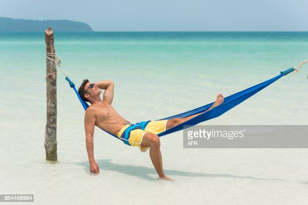 handsome man relaxing in a hammock on a secluded beach on vacation - asian six pack stock photos and pictures