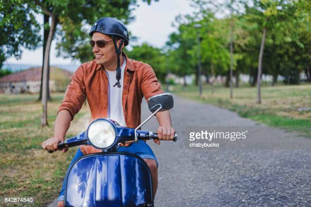 handsome man riding a vintage scooter - moped stock photos and pictures