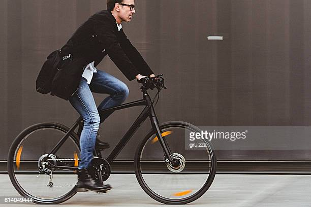 handsome man riding bicycle beside the grey wall - alleen één oudere man stockfoto's en -beelden