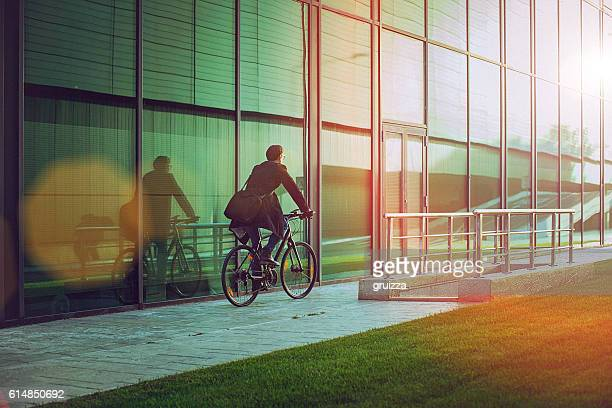 handsome man riding bicycle beside the modern office building - miljöbevarande bildbanksfoton och bilder