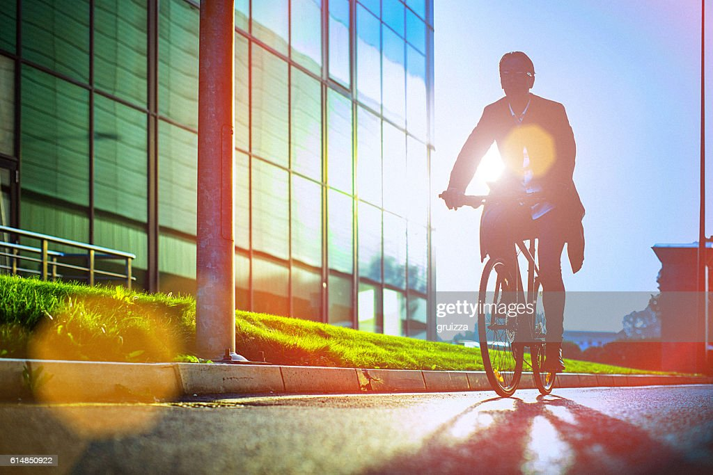Handsome man riding bicycle beside the modern office building : Stock-Foto