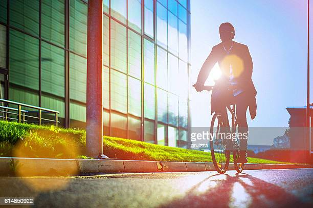 handsome man riding bicycle beside the modern office building - environmental issues stock pictures, royalty-free photos & images