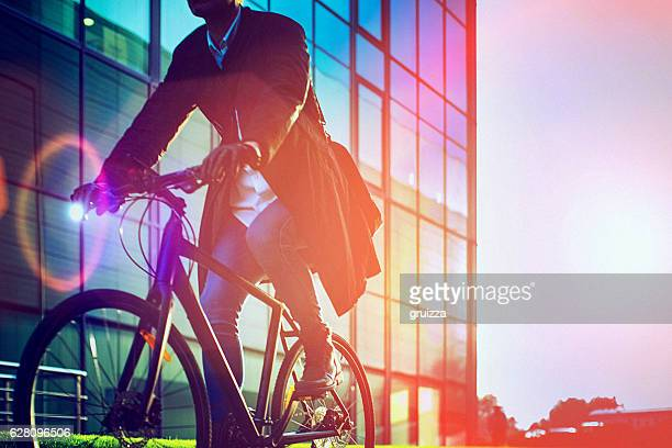 handsome man riding bicycle beside the modern office building - sustainability stock photos and pictures