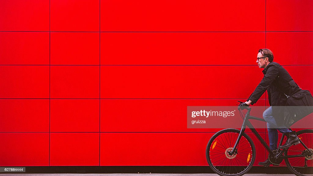 Handsome man riding bicycle beside the red wall : Stock Photo