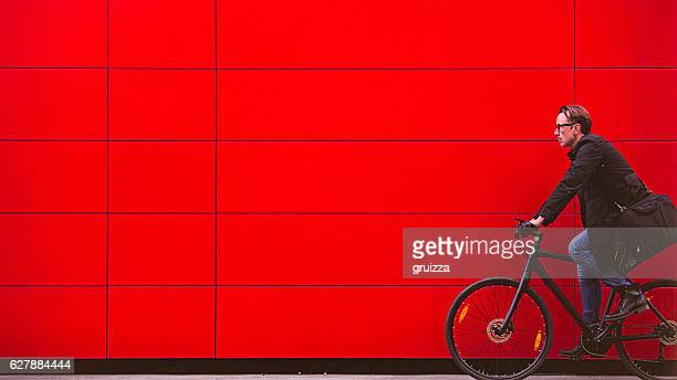 handsome man riding bicycle beside the red wall - red stock pictures, royalty-free photos & images