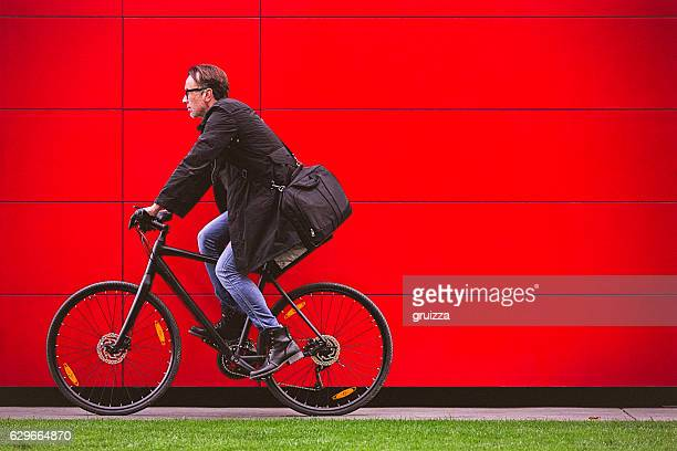 Handsome man riding bicycle beside the red wall
