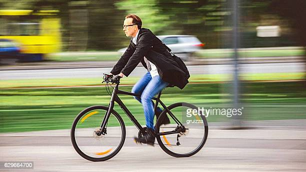 Handsome man riding bicycle on the way to work