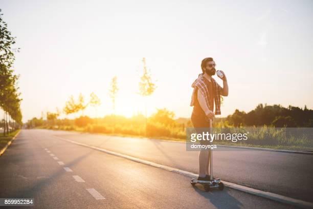 Knappe man van de push-scooter rijden en drinken koffie tijdens mooie zonnige dag