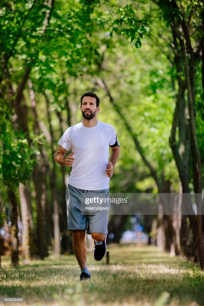 Handsome man running in nature alone : Stock Photo