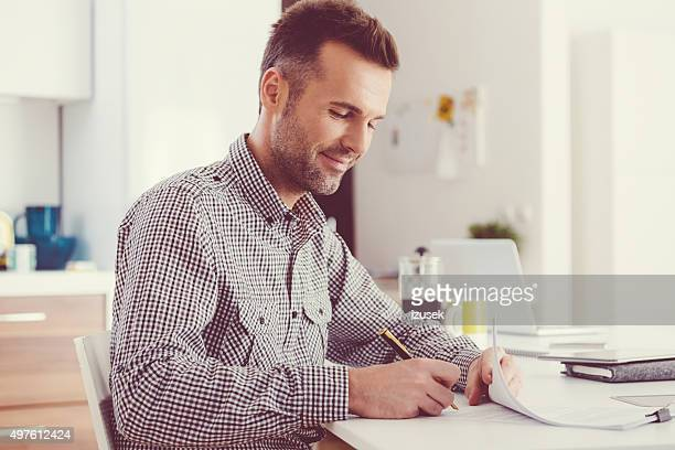 Handsome man signing documents, sitting at the table at home