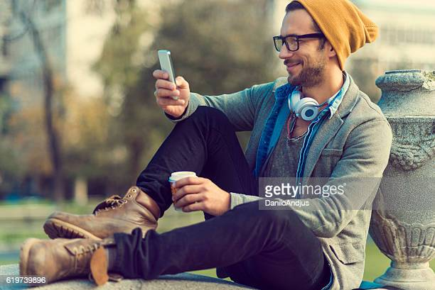 handsome man sitting in a park and using his smartphone