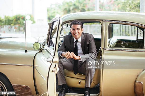 Handsome man sitting in an old classic car