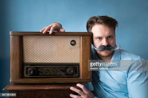 bel homme assis à côté de sa radio old-time - moustaches animales photos et images de collection