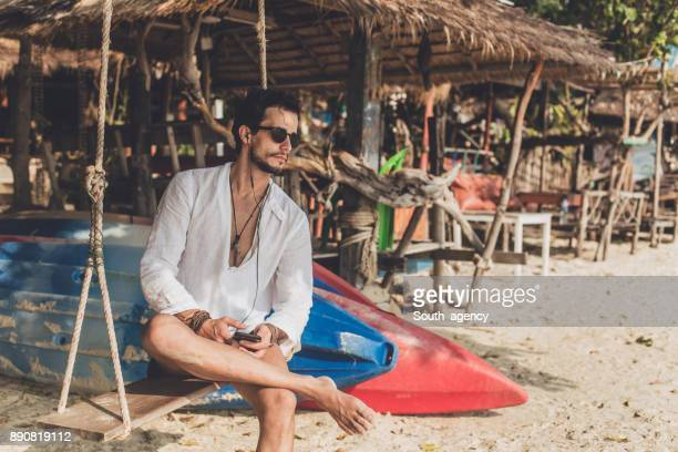 Handsome man sitting on a swing
