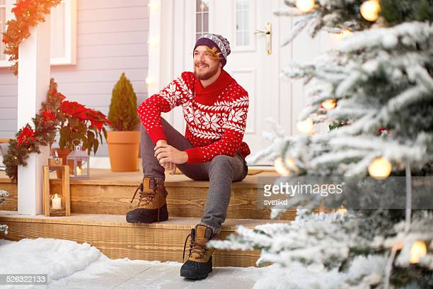Handsome man sitting on stairs in front of house.