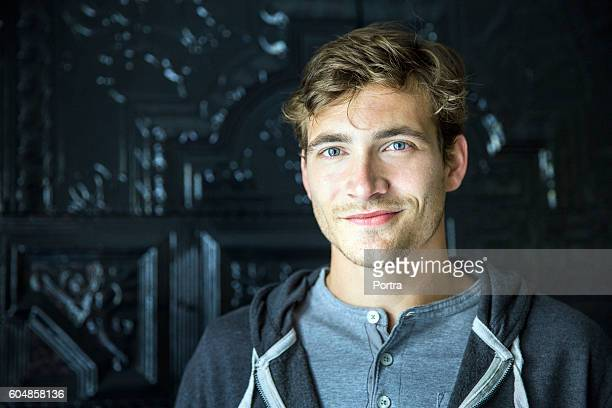 handsome man smiling against door - 25 29 jaar stockfoto's en -beelden