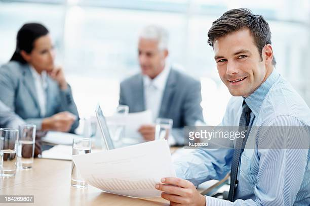 Handsome man smiling with colleagues in a meeting