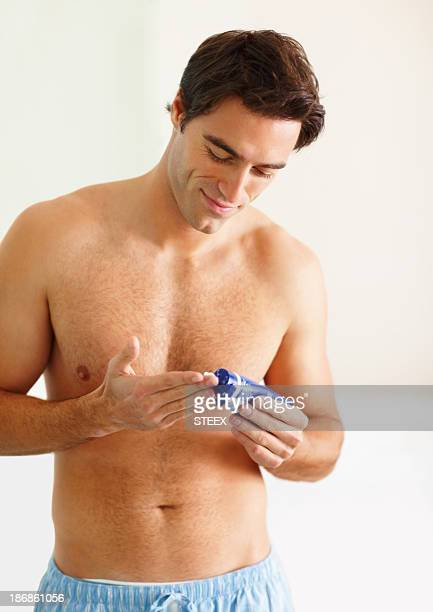 Handsome man squeezing out cream to his fingers