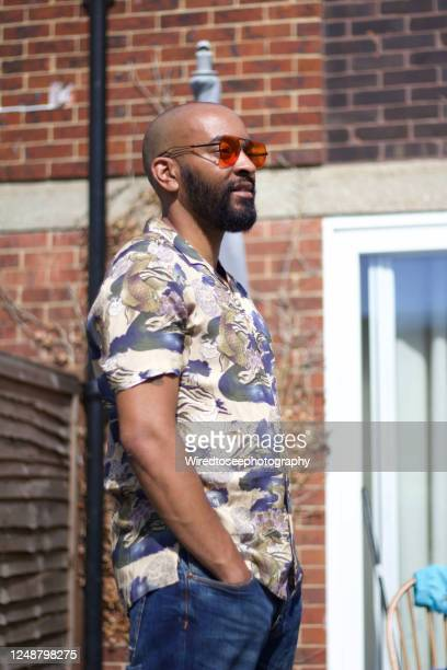 handsome man standing in garden wearing sunglasses - social justice concept stock pictures, royalty-free photos & images