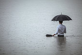 Handsome man standing in water and holding umbrella during rain