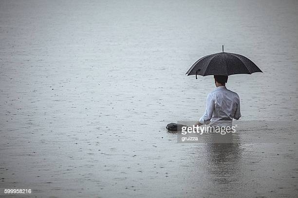 handsome man standing in water and holding umbrella during rain - flooding stock photos and pictures
