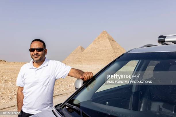 handsome man standing next to his car in front of giza pyramids - egypt stock pictures, royalty-free photos & images