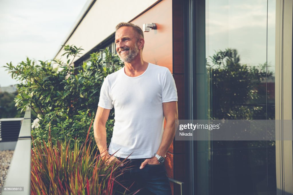 Handsome man standing on a balcony : Stock Photo